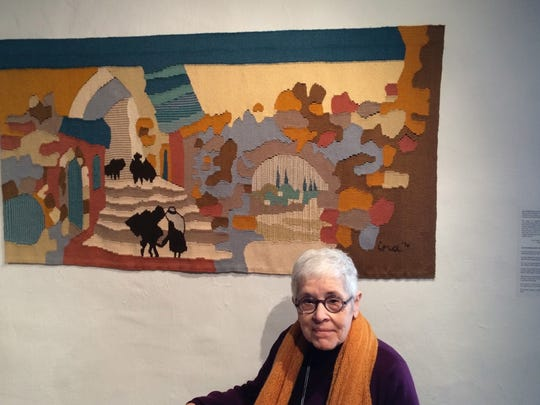 "Judaic fiber artist Ina Golub of Mountainside, sits in front of her 1970 tapestry titled ""Views of the Old City,"" now on display at a new contemporary tapestry exhibit at the Hunterdon Art Museum in Clinton."