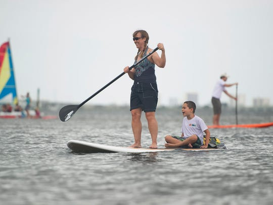 Debi Edmondson, of Stuart, shares her stand up paddle board with her friend Tristan Mattoon, 7, who has Asperger's syndrome, as they paddle around the Indian River Lagoon during the Stand up for Autism Stand Up Paddle Board Event in 2013. UK travel blogger Wanderlust Chloe tried paddle boarding for the first time when she visited Martin County.