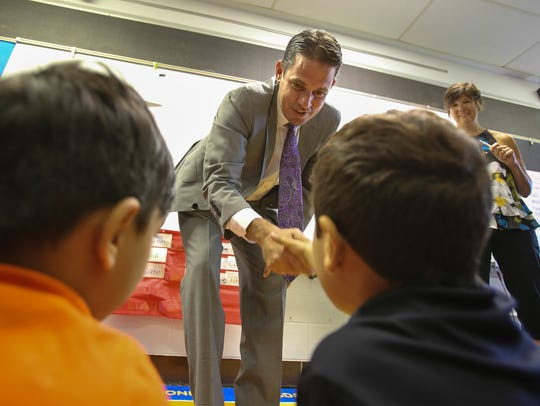 Marty Pollio shakes the hand of a student attending