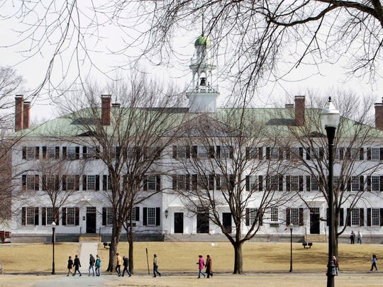 """FILE--In this March 12, 2012 file photo, students walk across the Dartmouth College campus green in Hanover, N.H. Authorities said Tuesday, Oct. 31, 2017, that three Dartmouth psychology professors are under criminal investigation for allegations of sexual misconduct. The previous week the college said the professors were put on paid leave and had their access to campus restricted due to allegations of """"serious misconduct."""" The college later told authorities it had received allegations of sexual misconduct. (AP Photo/Jim Cole, File)"""