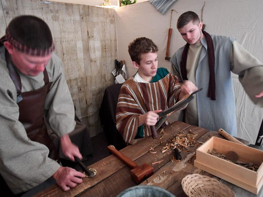 (L-R) Kirk Hayden, Kyle Curran, Justin Littrel hard at work in the village carpenter shop at the Journey to Bethlehem event held at Cairo United Methodist Church Sunday. The production takes visitors on a guided tour from Nazareth to Bethlehem with costumed characters and live animals, December 3, 2017.