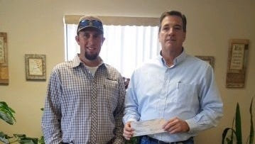 Catlin Curry of White Sands Construction Inc. hands a check to Tim Turri, Manager of Operations of New Mexico Gas Co.