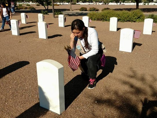A Girl Scout knelt in respect of a veteran before placing