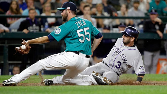 Colorado Rockies' Daniel Descalso (3) scores on a wild pitch as Seattle Mariners relief pitcher Tony Zych turns to try to put on a tag during the ninth inning of a baseball game Friday, Sept. 11, 2015, in Seattle.