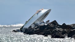 Investigators inspect the overturned boat carrying