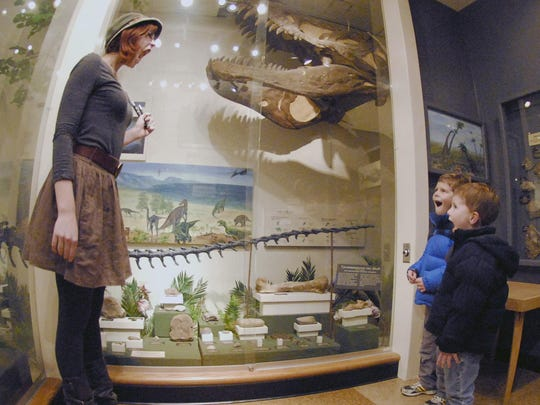 Kacey Tait, then a UWSP junior and tour guide at UWSP's Natural History Museum, opens her mouth wide, Tuesday Nov. 29, 2011, along with Keegan Hefferan (back) and Quintin Hefferan of Stevens Point, as they imitate the dinosaur in the display case as Tait gave a tour to the brothers at the museum during an open house.