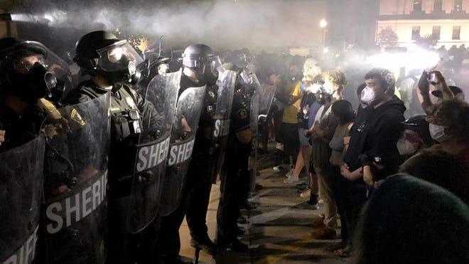 Protesters confront Kenosha County Sheriff's deputies outside the Kenosha Police Department on Aug. 23, 2020.
