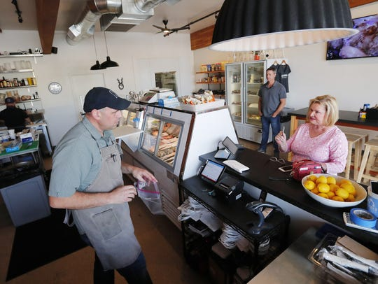 Ryan Laufenburger helps Pam Eklund at Nelson's Meat + Fish in Phoenix on April 10, 2018.