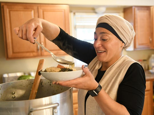 Summer Homayed ladles greens, called Nalta jute or tossa jute, onto rice preparing the dish mloukehia at her home in Dearborn Heights.