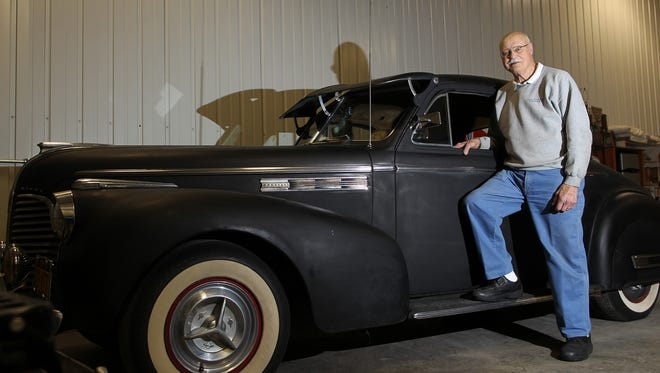 Dick Vitosh poses with his first car, a 1940 Buick coupe, at his auto detailing shop on Friday, Feb. 26, 2016.