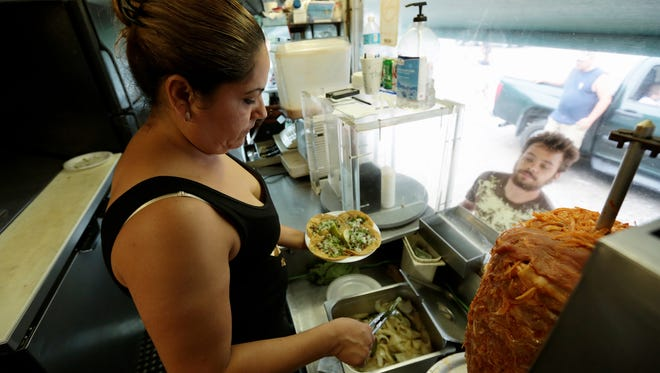 Nancy Paz, 42, of Detroit, fixes a taco for customers at Tacos El Caballo food truck earlier this month in southwest Detroit. Hillary Clinton's presidential campaign will conduct voter registration drives at eight southwest Detroit taco trucks Friday.