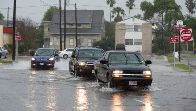 Cars drive thought standing water on Santa Fe Street at its intersection with Buford Street as rainfall caused flooding on Friday, March 10, 2017.