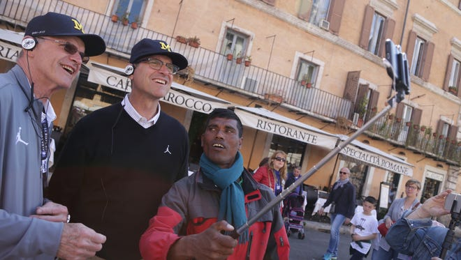 Michigan football coach Jim Harbaugh, center, and his father, Jack Harbaugh try a selfie stick after buying it from a street vendor in Rome on Monday, April 24, 2017.