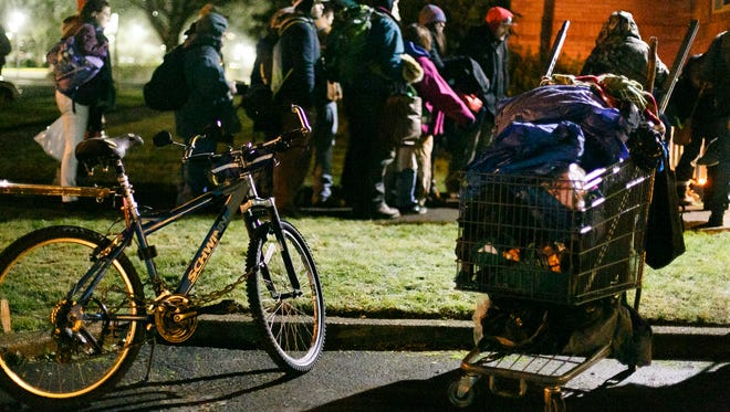 Carts full of belongings are left in the parking lot of First Presbyterian Church as people file into the downstairs sanctuary that opened as a warming shelter on Wednesday, Dec. 20, 2017, in Salem. Wednesday was the first night of the season that the shelter has opened.