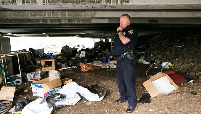 Salem Police Officer Bob Owings surveys what's left of a homeless camp under the Highway 22 overpass that crosses Mill Creek near Costco and Lowe's on Monday, Jan. 29, 2018. Officials cleared the camp, after the Oregon Department of Transportation posted temporary signs on Jan. 16 warning people to remove their property.