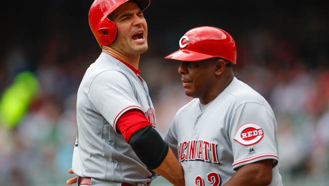 Joey Votto of the Cincinnati Reds is restrained by third base coach Billy Hatcher as he is ejected from the game in the first inning of an MLB game against the Atlanta Braves at SunTrust Park on June 27, 2018 in Atlanta, Georgia. (Photo by Todd Kirkland/Getty Images)