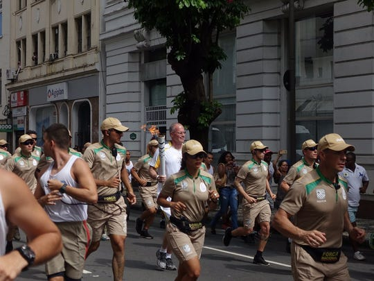 Surrounded by security officers, Bill Thompson, center, CFO of Nashville-based Bridgestone Americas, carries an Olympic torch May 24 in the streets of Salvador, Brazil, the host country for the 2016 Olympics.