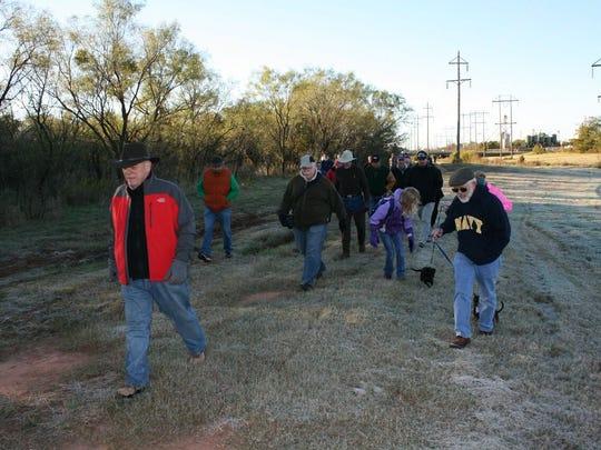 Mayor Norm Archibald leads the group as hikers trek along Cedar Creek on Saturday for the Mayor's Fall Hike 2016.