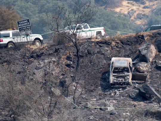 Law enforcement investigates a burned car off Highway