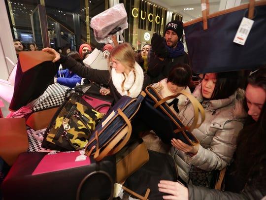 Shoppers go through a pile of handbags at Macy's Herald