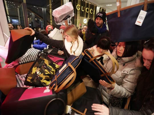 Shoppers go through a pile of handbags at Macy's Herald