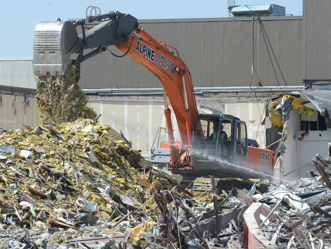 An excavator moves debris as construction continues at the Foothills Mall Thursday July 3, 2014.