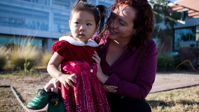 Jen Mayer (R) holds onto her soon to be adopted daughter Eve (L), 2, outside of the Juvenile Court Center on National Adoption Day Nov. 22, 2014 in Phoenix.
