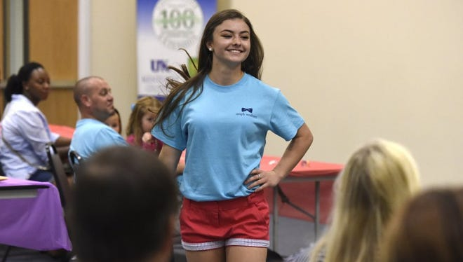 Tiffany Alley, 17, of Henderson, smiles as she models an athletic outfit on the runway during the Back to School Style Show at the Henderson County Cooperative Extension Service Education & Exposition Center in Henderson Saturday