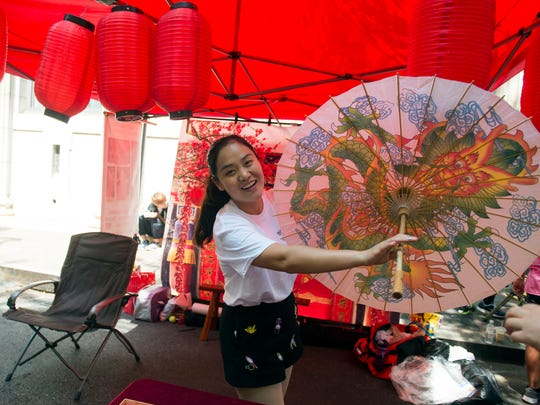 Maria Wang, Chinese teacher at West High School and L &N Stem Academy greet guests at the Chinese booth at the 4th Knox Asian Fest on Sunday, August 27, 2017.