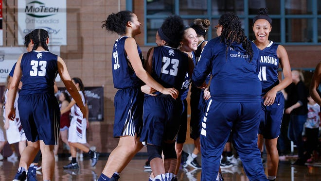 East Lansing players celebrate following their 49-43 win over Okemos Friday, Jan. 20, 2017, in Okemos, Mich.