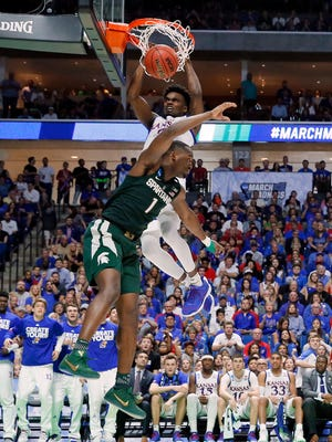 Kansas guard Lagerald Vick (2) dunks the ball over Michigan State' Joshua Langford (1) in the second half of a second-round game in the men's NCAA college basketball tournament in Tulsa, Okla., Sunday, March 19, 2017. (AP Photo/Tony Gutierrez)