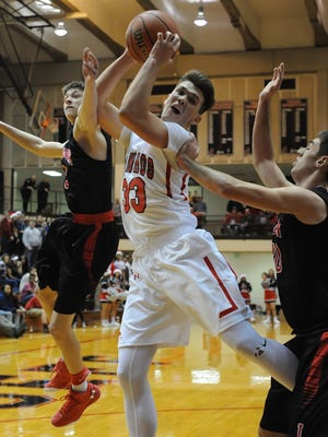 Lafayette Jeff Senior Keaton Schreckengast brings hauls a rebound in amid multiple Logansport defenders Friday night.