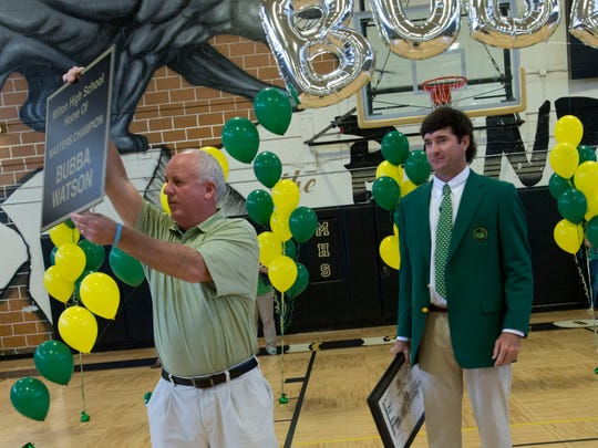 At left, Murry Rutledge, Milton High School's former athletic director, shows off a new sign that will hang in the school to recognize Bubba Watson, right, for his two  Masters Tournament  championships during a ceremony in 2014.