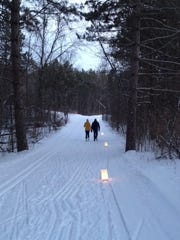 Candle luminaries light a trail in the Kettle Moraine State Forest-Northern Unit during a candlelight ski and snowshoe event.