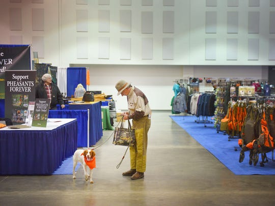 Steve Seibel looks around the National Pheasant Fest & Quail Classic with his dog Gracie, an American brittany, Friday, Feb. 16, at the Denny Sanford Premier Center.