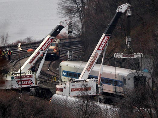 Cranes lift a derailed Metro-North train car in the Bronx borough of New York City. Federal authorities began righting the cars as they started their investigation into what caused the commuter train to derail on Sunday, killing four people and injuring more than 60 others.