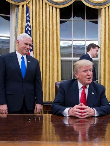 President Donald Trump (C) speaks to the press as he