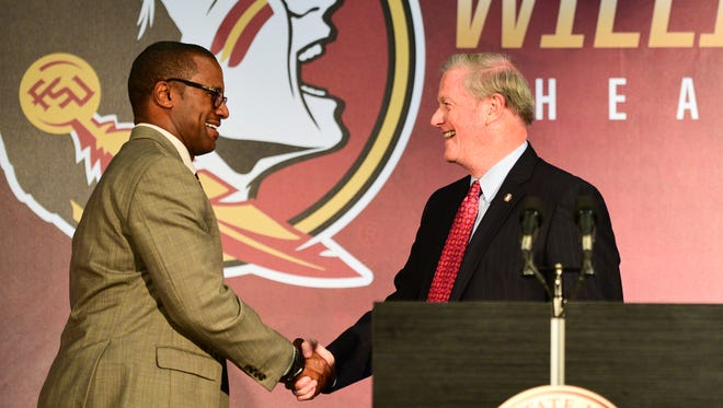 Florida State's new head coach Willie Taggart shakes hands with university president John Thrasher during a press conference at Doak Campbell Stadium.
