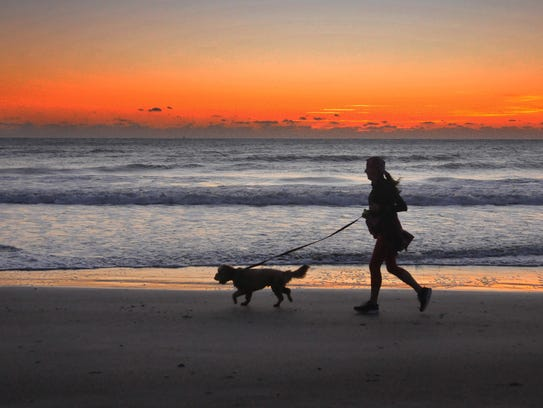 A woman and her dog run the beach just before sunrise