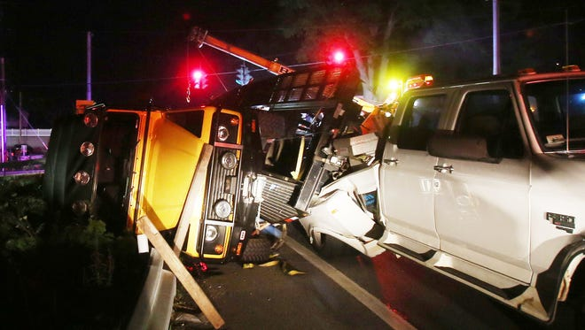 Workers from Bryson's Towing work to clear three vehicles from the side of Route 22 in North Salem after a transport trailer being towed by a pickup truck rolled over as it was turning from Hardscrabble road onto southbound Route 22 on July 28, 2016.