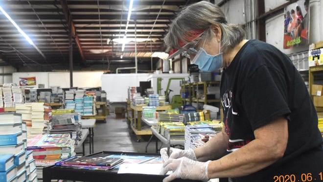 Volunteer Brenda Rawson checks titles off a Clarke County child's list of requested books. Another volunteer will take the completed order of a dozen books to the family's home.
