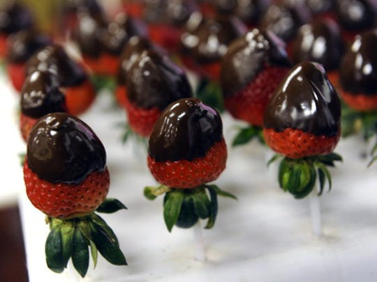 Hand dipped chocolate covered strawberries are prepared for the arrangements. All of the edible arrangements are completely hand made from the cutting of the fruit in designs such as hearts or daisies to dipping strawberries, bananas and apples into either white or semi-sweet chocolate. Employees at Edible Arrangements at 14241 West Colfax in Lakewood were busy as beavers today February 13th, 2011, getting edible bouquets of fruit ready for the Valentine's day rush. The crew were dipping thousands of strawberries in chocolate, blowing up mylar balloons with helium, and arranging baskets with all types of fruit for their arrangements including strawberries, bananas, honeydew and cantaloupe melons, grapes, apples and oranges. Many of them were dipped in white or semi-sweet chocolate for added deliciousness. Photo by Helen H. Richardson/The Denver Post  (Photo By Helen H. Richardson/The Denver Post via Getty Images)