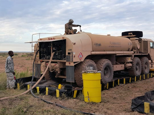 Sgt. John Mondragon, with Alpha Company, 127th Aviation Support Battalion, checks to see how much fuel is left in a fuel serving truck at a forward arming and refueling point.