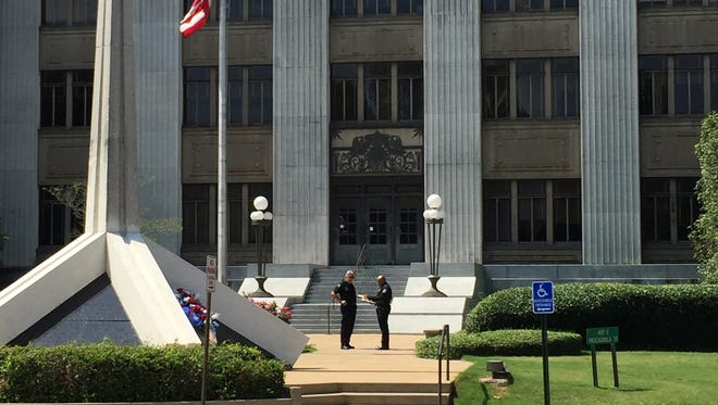 Jackson police officers stand in front of the Hinds County Courthouse.