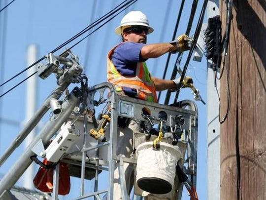Jeff Roach, an AT&T technician, adjusts lines on a pole.