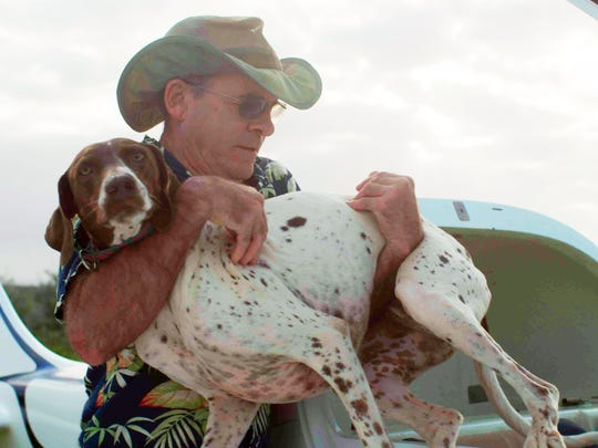 """Veterinarian Dr. Scott Sims, the star of Nat Geo Wild's new """"Aloha Vet"""" series, carries a dog next to the two-seater airplane he built from a kit, near his clinic on the island of Kauai in Hawaii. The series follows Sims on his rounds, which include patients on other islands — everything from dogs to horses and birds to sea turtles."""