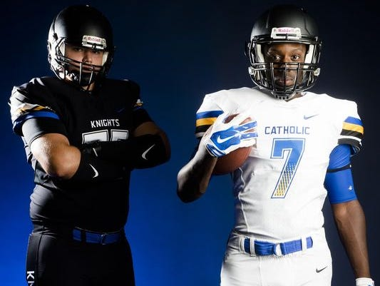 Catholic offensive lineman Brian Anderson and fullback Joshua Seals pose with their new uniforms.