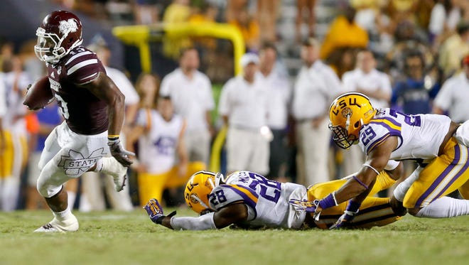 Mississippi State running back Josh Robinson (13)  escapes from LSU safeties Jalen Mills (28) and Rickey Jefferson (29) in the Bulldogs' win over the Tigers Saturday night.