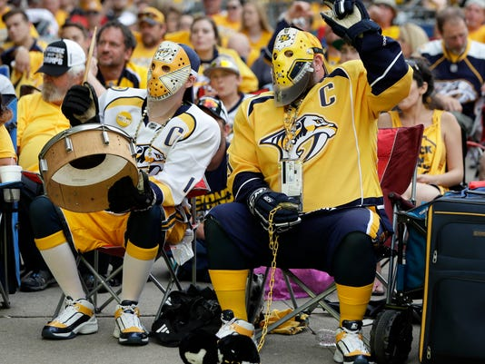 Nashville Predators fans Scott Sulfridge, left, and Chris Rickman, right, cheer as they watch the Predators play the Pittsburgh Penguins in Game 1 of the NHL Stanley Cup Finals at one of several viewing areas set up Monday, May 29, 2017, in Nashville, Tenn. (AP Photo/Mark Humphrey)