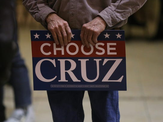 """A man holds a """"Choose Cruz"""" campaign poster during"""